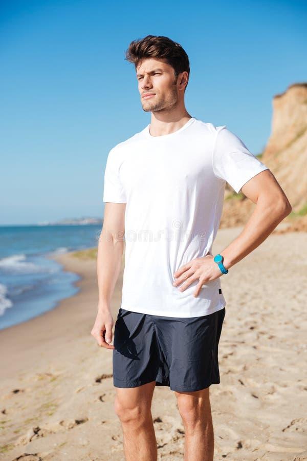 Durchdachter junger Sportler, der auf dem Strand steht und denkt stockfotografie