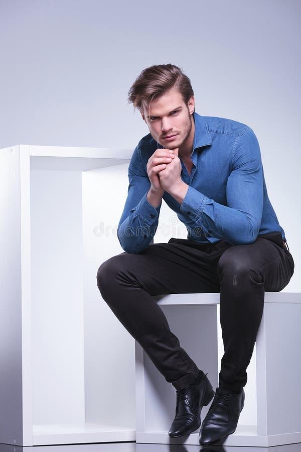 Durchdachter junger zufälliger Mann sitzt stockfoto