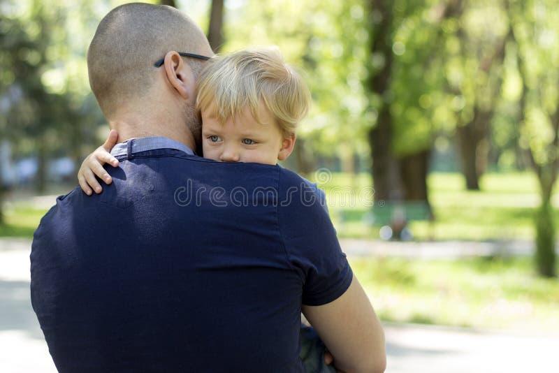 Durchdachter kleiner Junge auf Vater ` s Schulter Kopieren Sie Platz stockbild