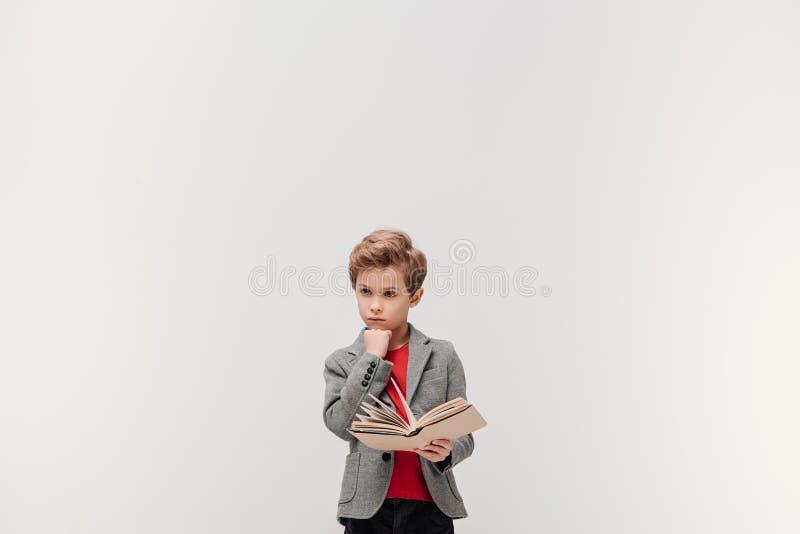 durchdachter kleiner Schüler mit Buch lizenzfreie stockbilder