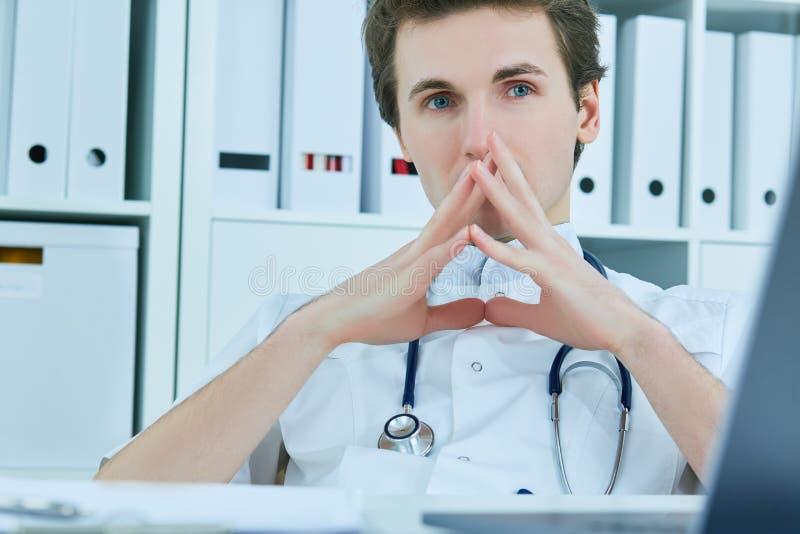 Durchdachter männlicher Doktor, der beim Sitzen Stuhl im Ärztlichen Dienst weg betrachtet stockfoto