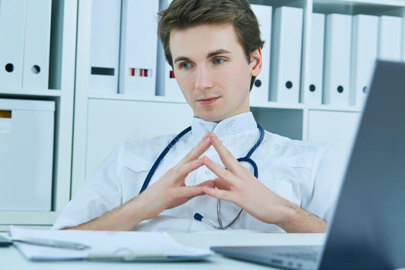 Durchdachter männlicher Doktor, der beim Sitzen Stuhl im Ärztlichen Dienst weg betrachtet stockbild