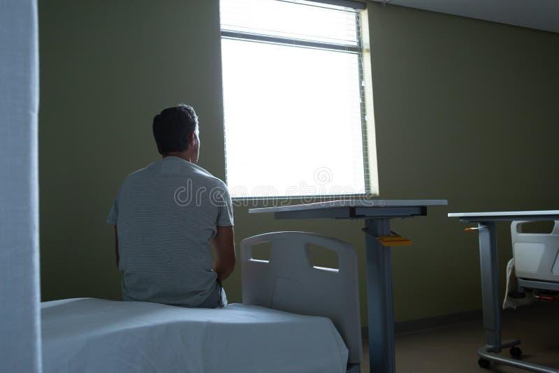 Durchdachter männlicher Patient, der auf Bett im Bezirk sitzt lizenzfreie stockbilder