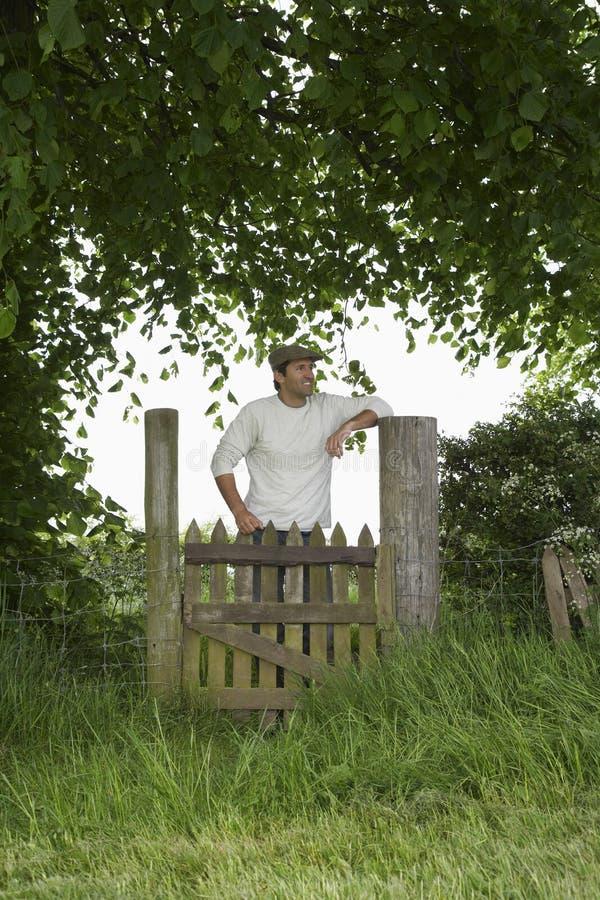Durchdachter Mann, der über Feld-Tor steht stockbild