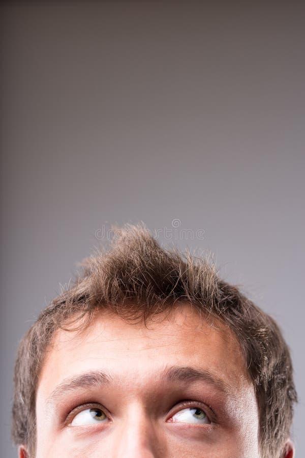 Durchdachter Mann, der oben schaut, um Kopienraum zu löschen lizenzfreies stockfoto