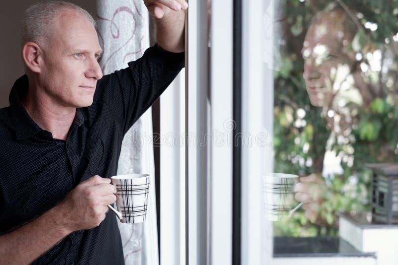Durchdachter Mann durch Fenster lizenzfreie stockbilder