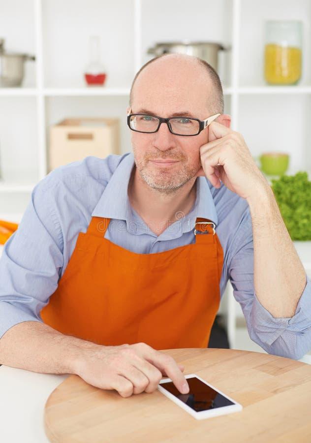 Durchdachter reifer Mann in der Küche mit dem Telefon lizenzfreies stockbild