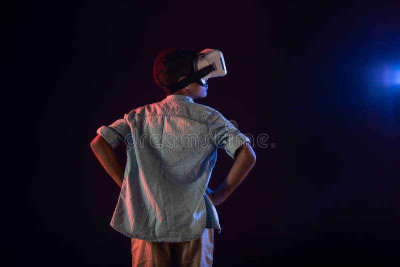 Durchdachter Schüler, der einen modernen VR-Kopfhörer trägt stockbilder