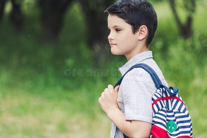durchdachter Schüler mit dem Rucksack, der weg schaut stockbilder