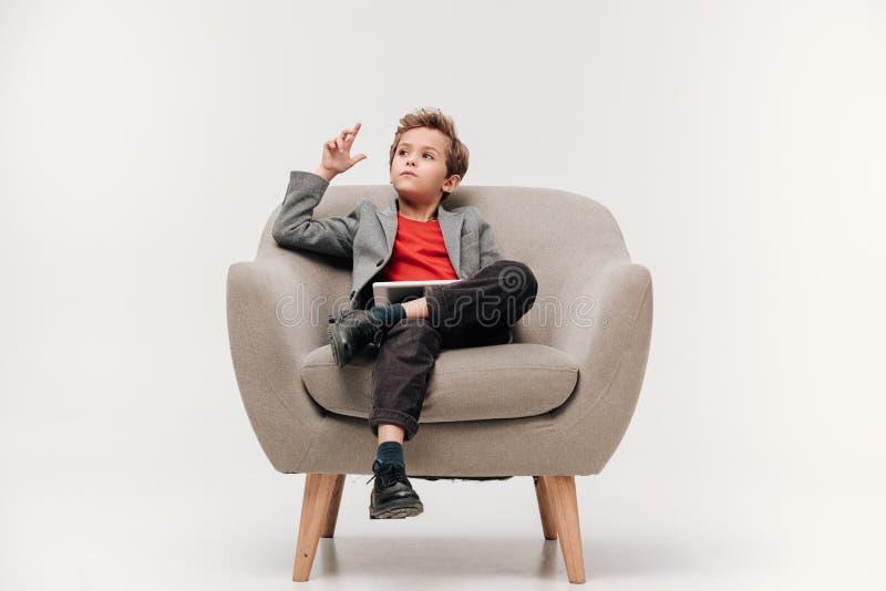 durchdachter stilvoller kleiner Junge, der im Lehnsessel sitzt lizenzfreies stockbild