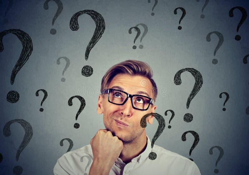 Durchdachter verwirrter gutaussehender Mann hat viele Fragen keine Antwort stockfotografie