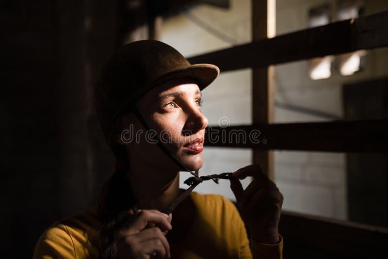 Durchdachter weiblicher Jockey, der weg im Stall schaut stockfotografie