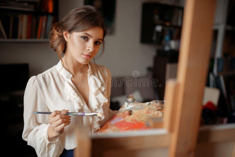 Durchdachter weiblicher Maler mit Farbpalette stockbild