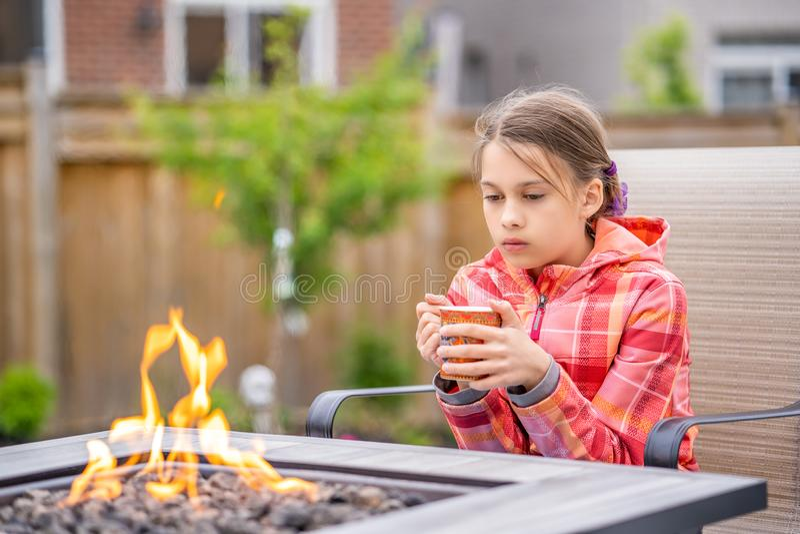 Durchdachtes junges Mädchen, das durch das Feuer sitzt lizenzfreies stockbild