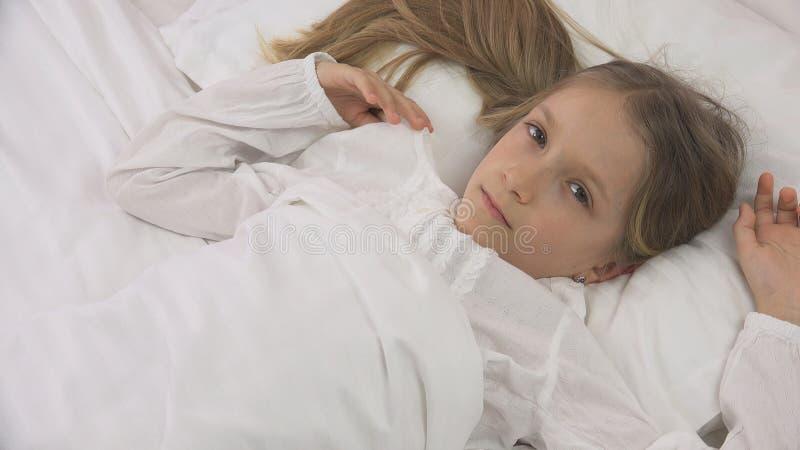 Durchdachtes Kind im Bett, nachdenkliches Kind, Mädchen kann nicht, schlafend im Schlafzimmer stockbilder