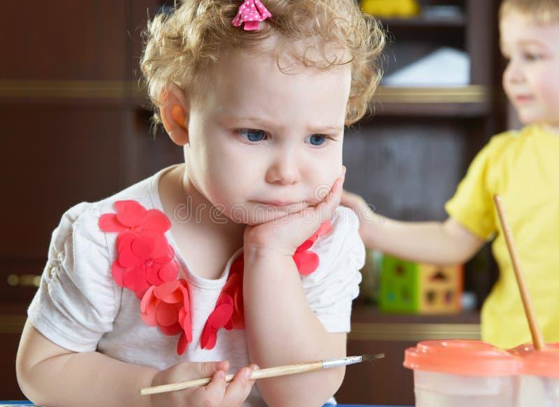 Durchdachtes kleines Mädchen mit Malerpinsel lizenzfreie stockfotos