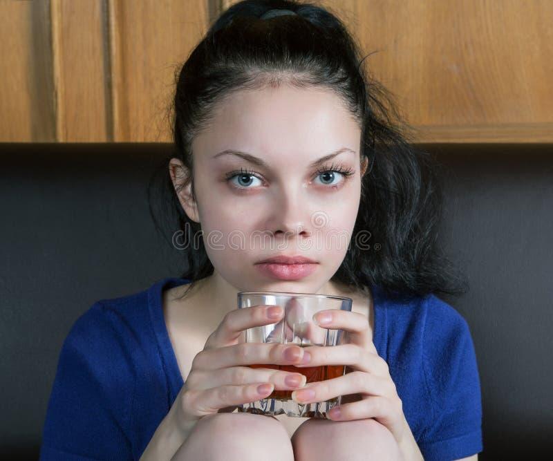 Durchdachtes Mädchen auf der Couch mit einem Glas lizenzfreie stockbilder