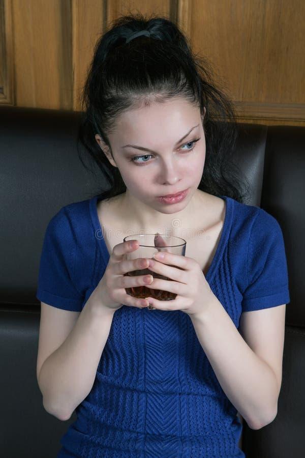 Durchdachtes Mädchen auf der Couch mit einem Glas lizenzfreie stockfotos