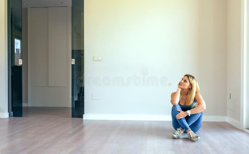 Durchdachtes Mädchen, das in einem Wohnzimmer sitzt lizenzfreie stockbilder