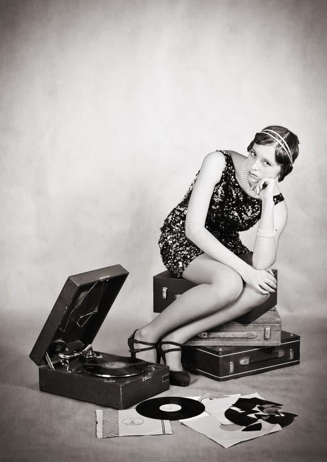 Durchdachtes Mädchen mit einem Grammophon weinlese lizenzfreies stockfoto