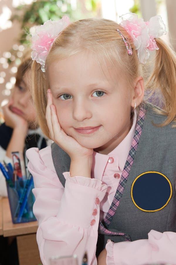 Durchdachtes Schulmädchen im Klassenzimmer lizenzfreie stockbilder
