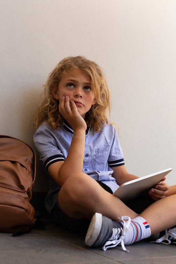 Durchdachtes Schulmädchen mit digitaler Tablette und der Schultasche, die auf dem Boden sitzt lizenzfreie stockfotografie