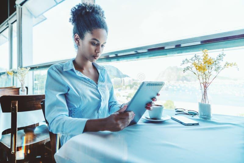 Durchdachtes schwarzes Freiberuflermädchen im Restaurant mit digitalem tabl lizenzfreie stockfotos