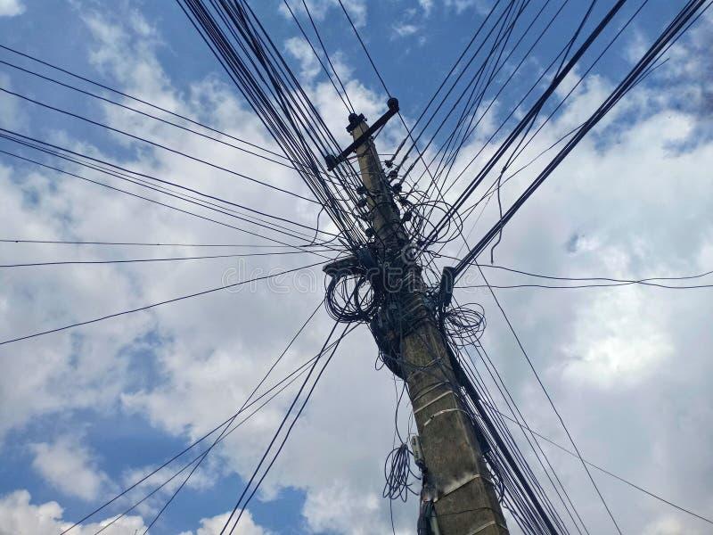 Durcheinandergebracht herauf Kabel auf einem konkreten Pfosten mit blauem Himmel auf dem Hintergrund lizenzfreies stockfoto