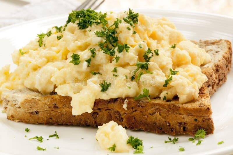 Durcheinandergemischte Eier auf Toast stockbilder
