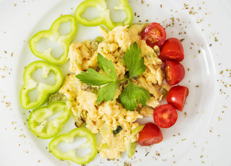 Durcheinandergemischte Eier mit Paprika, Kirschtomaten und Sellerieblättern lizenzfreie stockbilder