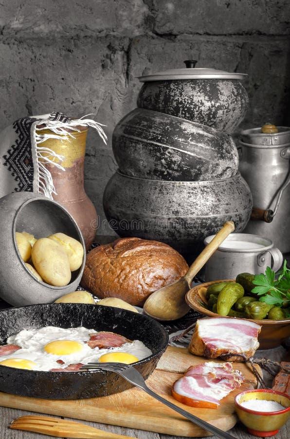 Durcheinandergemischte Eier mit Speck, gekochten Kartoffeln und Essiggurken lizenzfreie stockfotos