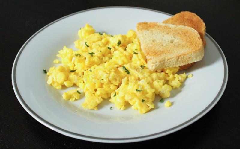 Durcheinandergemischte Eier mit Toast lizenzfreie stockfotos