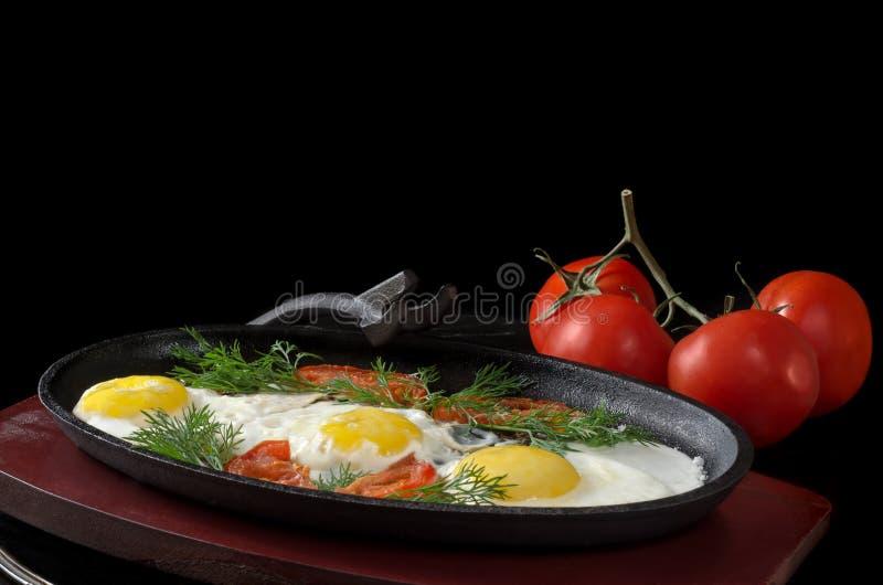 Durcheinandergemischte Eier mit Tomaten und ganzen Tomaten, auf einem schwarzen Hintergrund lizenzfreie stockfotos