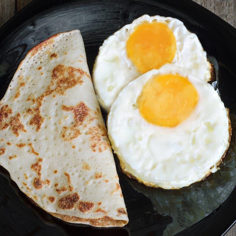 Durcheinandergemischte Eier und Pfannkuchen auf einem Schwarzblech lizenzfreies stockfoto