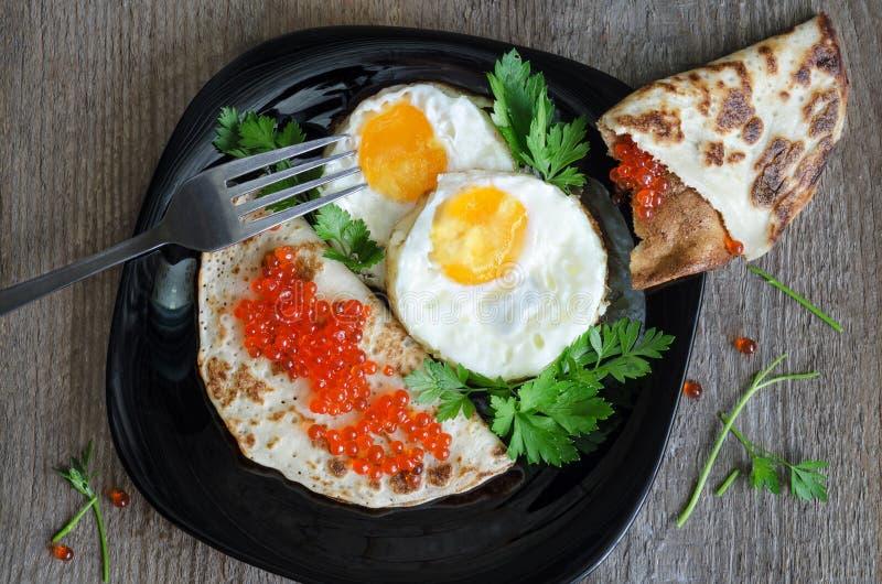 Durcheinandergemischte Eier und Pfannkuchen mit Kaviar auf einem Schwarzblech stockbilder