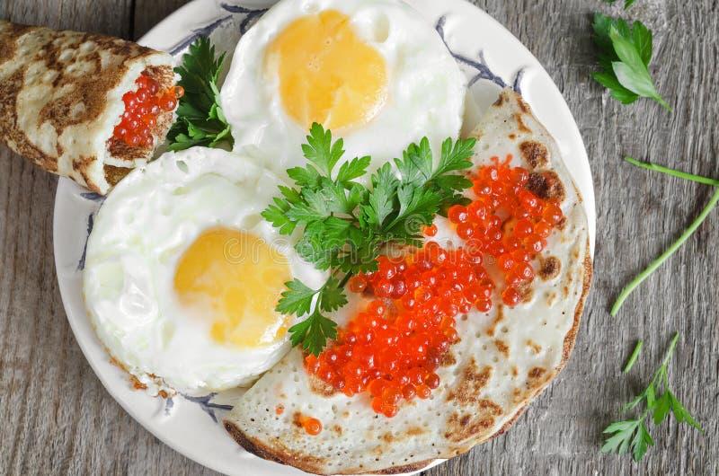 Durcheinandergemischte Eier und Pfannkuchen mit rotem Kaviar stockbilder