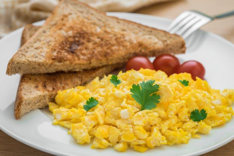 Durcheinandergemischte Eier und Toast auf Platte stockbilder