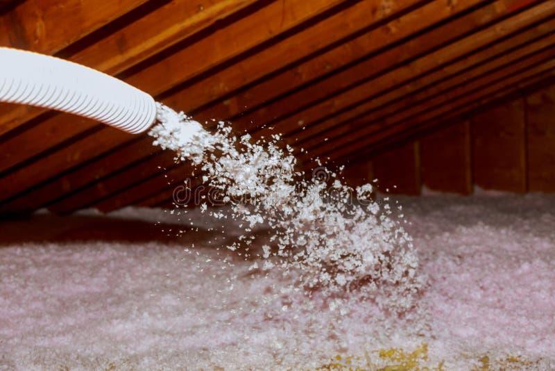Durchgebrannte Fiberglas-Sprühisolierung für Dach - Technikersprühschaumisolierung unter Verwendung des Mehrzahl- Teilgewehrs stockfotografie