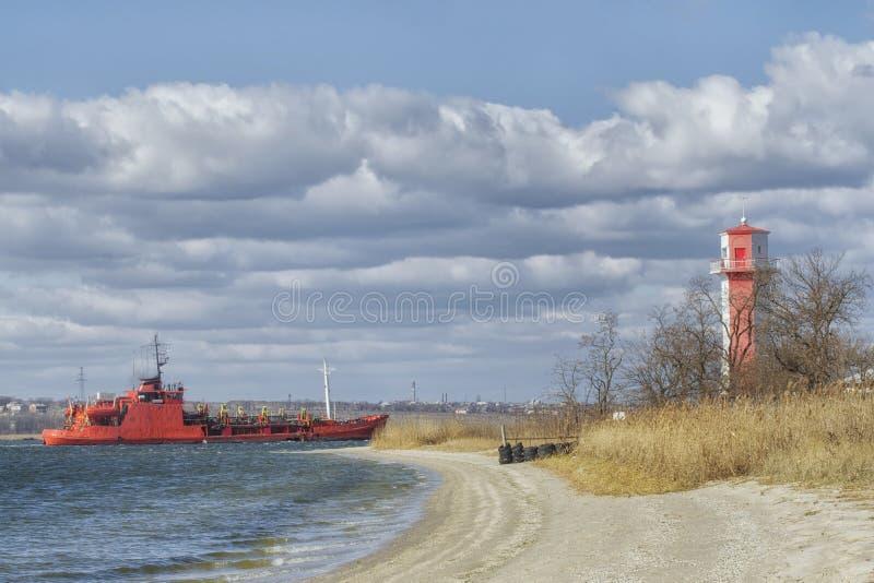 Durchläufe eines große Frachtschiffs nahe dem Leuchtturm zum Hafen eines Containerbahnhofs im Mykolaiv-Seehafen stockbilder