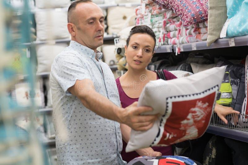 Durchnässte Paare, die zu Hause Dekorationsspeicher der Stoffe wählen lizenzfreie stockfotos