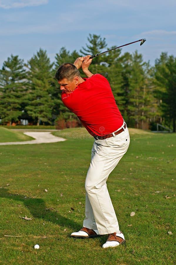 Durchschwung des Golfspielers stockfoto