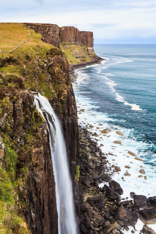 Durchtränken Sie felsige Küstenlinie mit Wasserfall stockfotografie