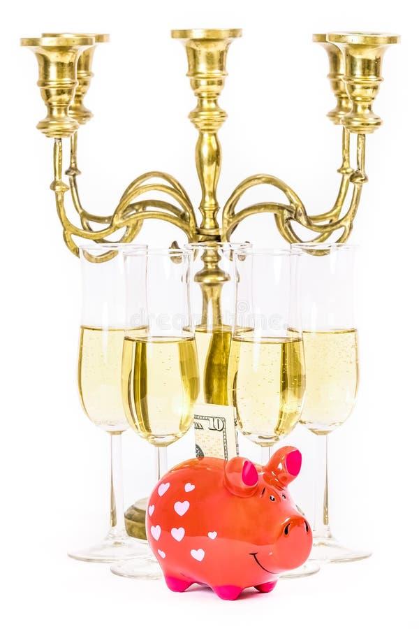 Dure levensstijl Glazen champagne, spaarvarken en candel stock foto's