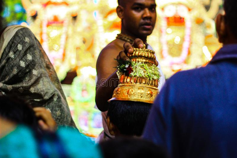 Durgapur, il Bengala Occidentale, India Luglio 2018 un Purohit Panda Blessing un patito con il cappello dorato sacro al festival  fotografia stock