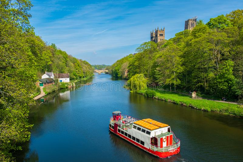 A cruise boat cruises along River Wear on a beautiful spring day in Durham, United Kingdom. Durham, United Kingdom - April 30, 2019: A cruise boat cruises along royalty free stock photo