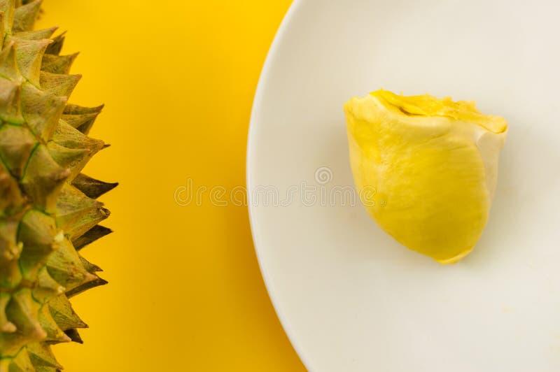 Durian em uma placa branca com a casca verde do ponto e backgr amarelo foto de stock royalty free