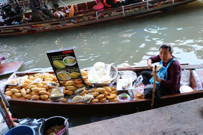 Durian och mango med säljaren för klibbiga ris på fartyget i kanalen på Damnoen Saduak som svävar marknaden royaltyfri bild