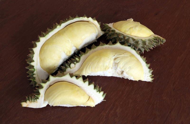 Durian op de houten lijst, vier stukken wordt gepeld dat Durian is een ovaal doornig tropisch fruit die een romige pulp bevatten stock afbeeldingen