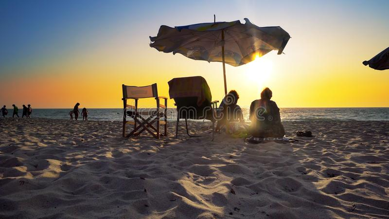 senior couple of old man and woman sitting on the beach watching sunset royalty free stock photography