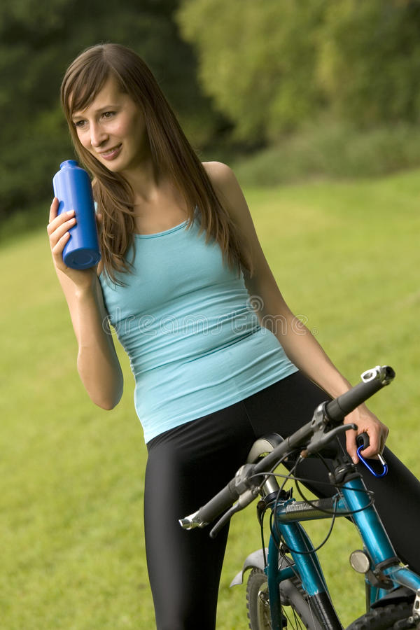 Durstige Frau auf Fahrrad lizenzfreie stockfotografie